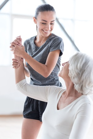 pleasurable: Pleasurable training. Delighted attractive slim coach holding a hand of the woman and smiling while looking at her