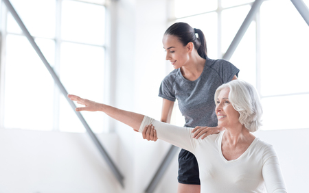 elated: Workout with a fitness coach. Nice elated grey haired woman standing in front of her coach and stretching out her arm while having aerobics classes Stock Photo