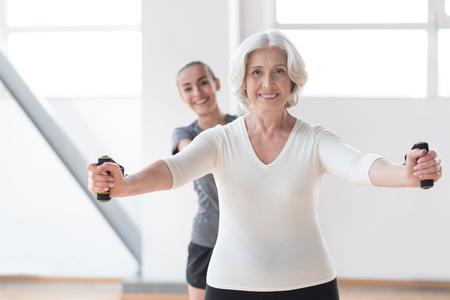 keeping fit: Keeping fit. Optimistic joyful nice woman looking at you and smiling while standing in front of her couch