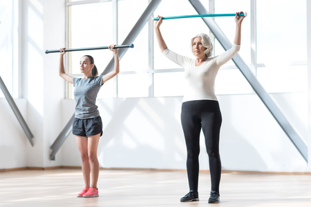 Focused on the task. Nice persistent hard working women standing together in a gym and holding their gymnastic sticks up while concentrating on the workout Stock Photo
