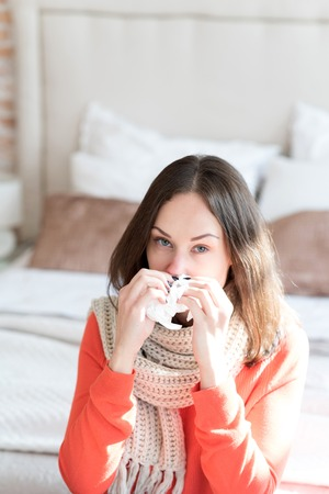 good looking woman: Suffering from running nose. Depressed tired good looking woman sitting on a bed and holding a tissue while having a cold