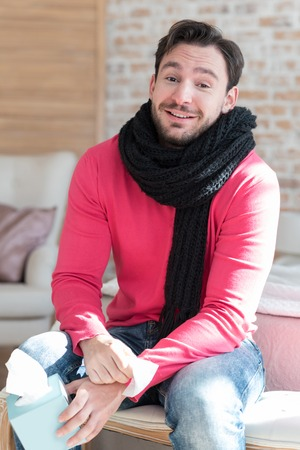 warmth: Need to stay in warmth. Pleasant optimistic young man sitting on the bed and wearing a scarf while being ill Stock Photo