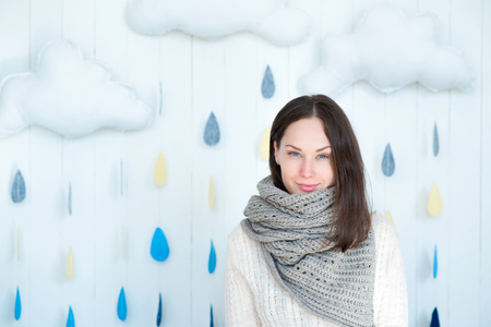 warmth: I am in warmth. Good looking delighted young woman wearing a warm scarf and smiling while standing against the rainy background