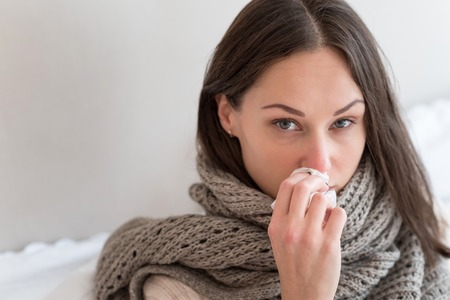 Flu symptoms. Depressed cheerless young woman holding a paper tissue and wiping her nose while suffering from flu Stock Photo