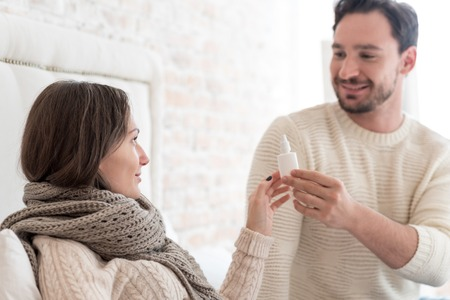 holding nose: Take your medicine. Good looking delighted positive man holding nose drops and giving them to his ill girlfriend while caring about her