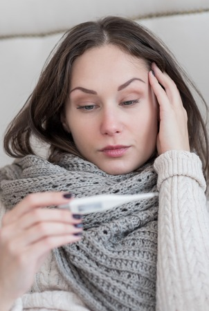 miserable: Being sick. Cheerless gloomy ill woman holding a body thermometer and looking at it while suffering from a high fever Stock Photo