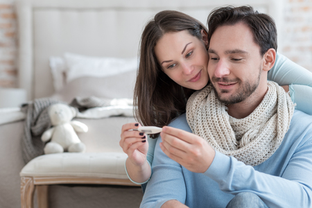 Feeling better. Pleasant delighted young couple holding a body thermometer and smiling while feeling much better