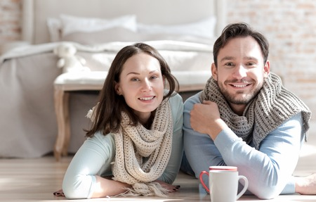 Positive mood. Nice joyful optimistic couple looking in front of them and smiling while being in a great mood Stock Photo