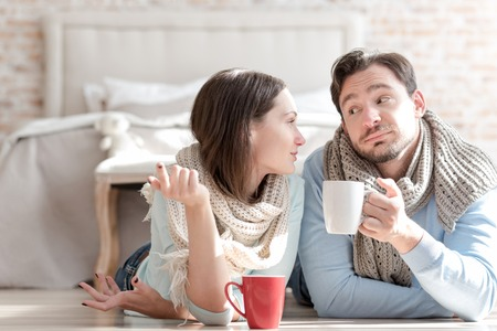 good looking: Involved in the conversation. Cheerful good looking nice couple looking at each other and having tea while having a conversation. Stock Photo