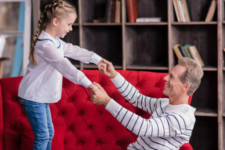 Involved in fun . Smiling girl standing on the couch and holding hands of her grandfather while resting together