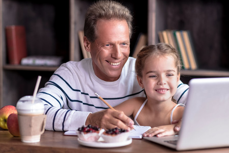Surfing cartoons in the Internet .Happy little girl sitting at the table with her grandfather while looking at the laptop and drawing