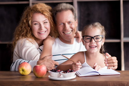 delighted: We happy together. Delighted little girl sitting at the table with her grandparents while drawing