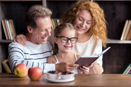family discussion: We enjoy reading together. Delighted little girl sitting at the table with her grandparents while reading and having fun at home