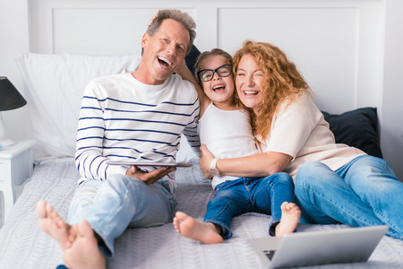 child girl: We having fun. Smiling little girl sitting on the bed with her grandparents and having fun at home