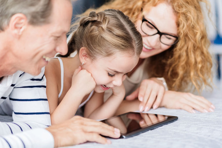 We watching funny cartoon. Amused little girl lying on the bed with her grandparents while looking at the tablet and having fun at home Stock Photo