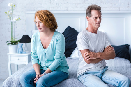I do not understand you. Angry husband and wife sitting back to back on the bed with crossed arms Archivio Fotografico