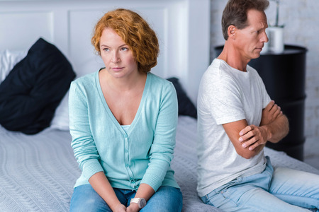 choleric: Quarrelsome. Irritated husband and wife sitting back to back on the bed with crossed arms Stock Photo