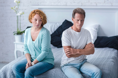 choleric: We want divorce. Irritated husband and wife sitting back to back on the bed with crossed arms Stock Photo