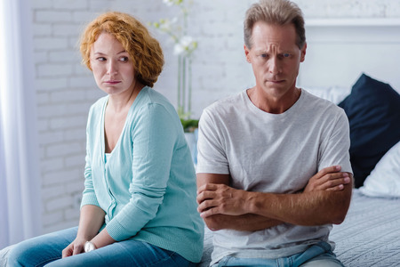 choleric: I beg you to forgive. Upset husband and wife sitting back to back on the bed with crossed arms while having a quarrel