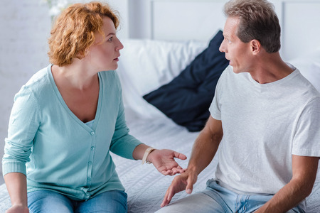 choleric: How can you do to me like this. Shocked couple sitting on the bed while arguing