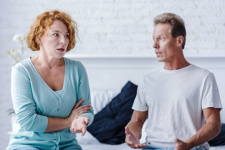 choleric: Dont you hear me. Shocked senior couple sitting on the bed while arguing at home