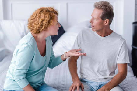 irritated: You are wrong. Irritated senior couple sitting on the bed while arguing at home Stock Photo