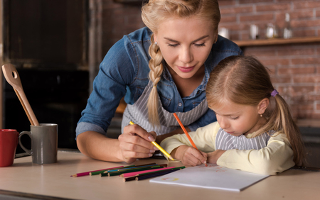 delighted: Happy free time. Delighted cheerful happy woman drawing with her daughter while sitting at the table and expressing joy in the kitchen