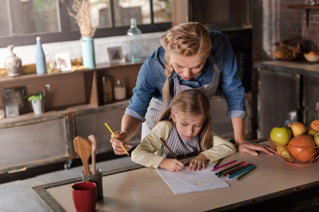 maternal: Joyful weekend . Delighted beautiful happy woman drawing with her little daughter while standing near the table and expressing joy in the kitchen
