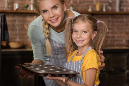 Happy cooking hours. Smiling pleasant little girl putting the pastry in the oven while standing in the kitchen and helping her mother
