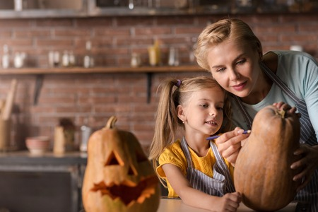 potěšen: Lets do it together. Pleasant involved little girl drawing a face on the pumpkin for Halloween with her mother while standing in the kitchen near the table and expressing joy
