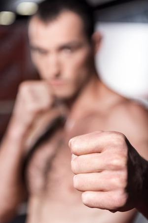 knockdown: Knock-down. Close-up portrait of strong muscular kick boxer pointing his fist forward.