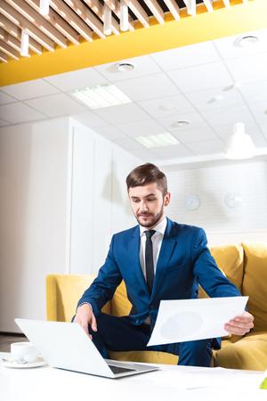 diligente: trabajador diligente. Agradable de negocios concentrado guapo sentado en el sofá y trabaja con los papeles, mientras que usando la computadora portátil