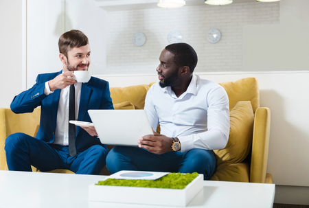 Positive atmosphere. Cheerful delighted professional colleagues sitting on the couch and discussing project while working in the office Stock Photo