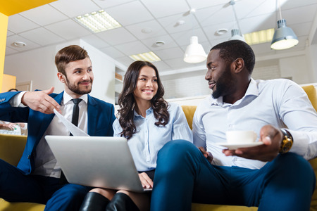 Rise your mood. Glad emotional professional colleagues sitting on the sofa and discussing project while sharing ideas Stock Photo