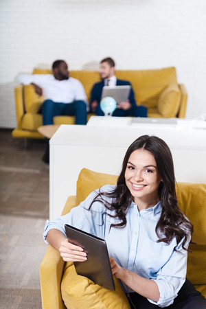 Bright emotions. Top view of beautiful positive woman using tablet and sitting on the couch while her colleagues communicating in the background