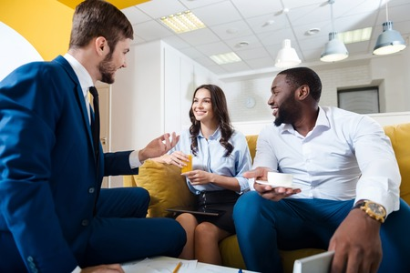 Rapid lifestyle. Joyful delighted colleagues talking and discussing project while sitting in the office Stock Photo