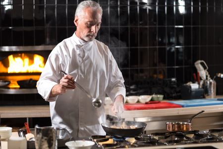 working hours: Working hours. Concentrated involved hardworking chef mixing mushrooms on the frying pan while standing near the stove in the kitchen of the restaurant and cooking Stock Photo