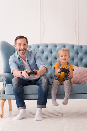 Father and daughter. Happy handsome bearded man sitting on the sofa and smiling while playing video games with his daughter