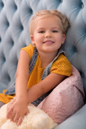 Feeling comfortable. Nice sweet delighted girl stretching her arms forward and holding a teddy bear while sitting on the sofa Reklamní fotografie