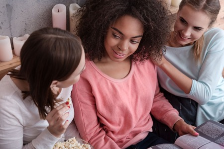 opinions: Share opinions. Delighted involved young girls reading the magazine and eating popcorn while lying on the bed at home and sharing opinions Stock Photo