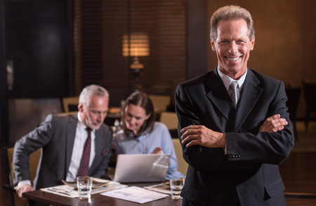 working hours: Happy working hours. Smiling delighted pleasant man with crossed arms standing in the restaurant while being near his business partners working with a laptop and discussing a project in the background Stock Photo