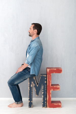 Home decor. Serious handsome bearded man sitting half face on the large letter M and looking in front of him while having a rest