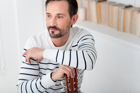 Thoughtful look. Handsome serious bearded man holding a musical instrument and leaning on it while thinking about something