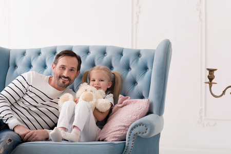 ponytails: Homely atmosphere. Nice sweet blonde girl having ponytails and holding her teddy bear while sitting on the couch Stock Photo