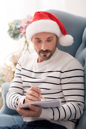 manhood: Concentrated on the activity. Handsome serious brunette man wearing a Santa hat and writing a list of presents for Christmas