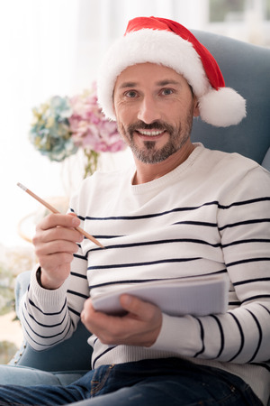 anticipation: Pleasant anticipation. Nice attractive joyful man holding a pencil and paper and smiling while writing a list of Christmas presents Stock Photo