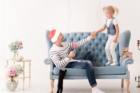 constant: Constant support. Nice pleasant loving father wearing a Santa hat and looking at his daughter while holding her hand