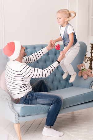 A moment in the air. Happy positive cute girl holding her fathers hands and laughing while jumping on the couch Stock Photo