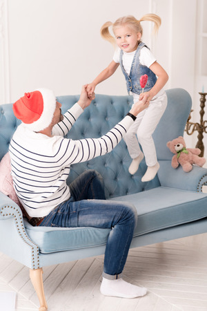 Jumping in the air. Nice happy active girl jumping on the sofa and holding his fathers hands while taking pleasure in this activity