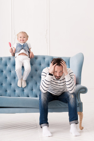 naughty child: Naughty child. Sad handsome thoughtful father sitting on the couch and holding his head while thinking what to do with his daughter Stock Photo